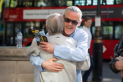 "© Licensed to London News Pictures. 08/05/2018. London, UK. Paddy Hill of the Birmingham 6 (facing away) and Patrick Maguire of the Maguire 7 (blue shirt) hug as they arrive at the Supreme court to support Sam Hallam (not pictured) who is appealing for ""miscarriage of justice"" compensation. Hallam spent over seven years in jail after he was wrongly sentenced to life in 2005 for a gang-related murder in north London that he did not commit. Photo credit : Tom Nicholson/LNP"