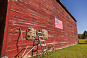 A old wooden barn decorated with an American flag on the Quilt Trails in Prices Creek, North Carolina. The quilt trails honor handmade quilt designs of the rural Appalachian region.