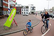 in Utrecht fietsen mensen voorbij een campagnebord van GroenLinks. De partij wil duidelijk maken dat ze ruim baan voor fietsers wil maken en dat fietsers voorrang moeten hebben.<br /> <br /> In Utrecht cyclists past a campaign sign of GroenLinks. The political party wants to make clear that it wants to make room for cyclists and cyclists must take precedence.