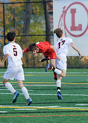 Belmont's Logan Wilder collides with Stevens Parker Moore heading the ball away from the goal in the NHIAA Division III semi-final game at Laconia High School on Wednesday, November 2, 2016.  (Alan MacRae/for the Laconia Daily Sun)