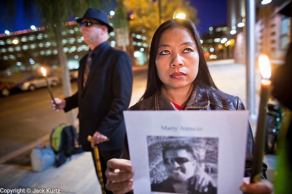 """04 JANUARY 2012 - PHOENIX, AZ:   LOVELY DYSON holds a candle during a vigil for Marty Atencio in front of the Maricopa County Jail in Phoenix on January 4. Atencio died in a Phoenix hospital on Dec 20, 2011. He was arrested by Phoenix police a few days earlier after he exhibited """"bizarre"""" behavior on the street. He was booked into the Maricopa County Jail. During the booking process he was tackled by Maricopa County Detention Officers and repeatedly hit was a Taser stun gun. He was later found unconscious in a holding cell and transferred to a hospital, where he died four days later. An autopsy showed no signs of illegal drugs or intoxication and a video from the jail showed that Atencio was not violent in the jail. His family has hired a lawyer and may sue the Maricopa County Sheriff's Department, which administers the jail.      PHOTO BY JACK KURTZ"""