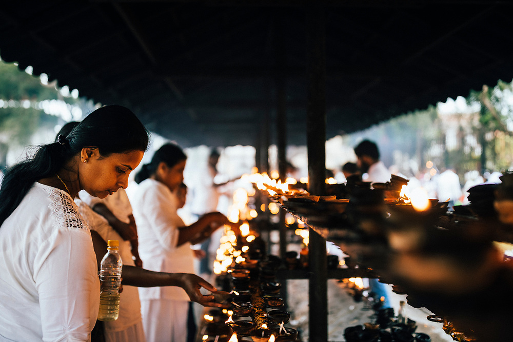 Kandy, Sri Lanka -- January 31, 2018: People light candles at the Temple of the Tooth.