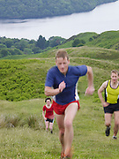 Three people running up hillside