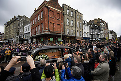 © Licensed to London News Pictures. 31/03/2018. Cambridge, UK. The funeral procession leaves the church, through the streets of Cambridge, surrounded by mourners and members of the public. The funeral of Stephen Hawking at Church of St Mary the Great in Cambridge, Cambridgeshire. Professor Hawking, who was famous for ground-breaking work on singularities and black hole mechanics, suffered from motor neurone disease from the age of 21. He died at his Cambridge home in the morning of 14 March 2018, at the age of 76. Photo credit: Ben Cawthra/LNP