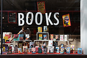 An employee of London bookshop retailer, Foyles makes changes to the window of the books and literature retailer on Charing Cross Road, during the Coronavirus pandemic at a time when only some retailers and business are re-opening while office workers still largely work from home, on 2nd September 2020, in London, England.