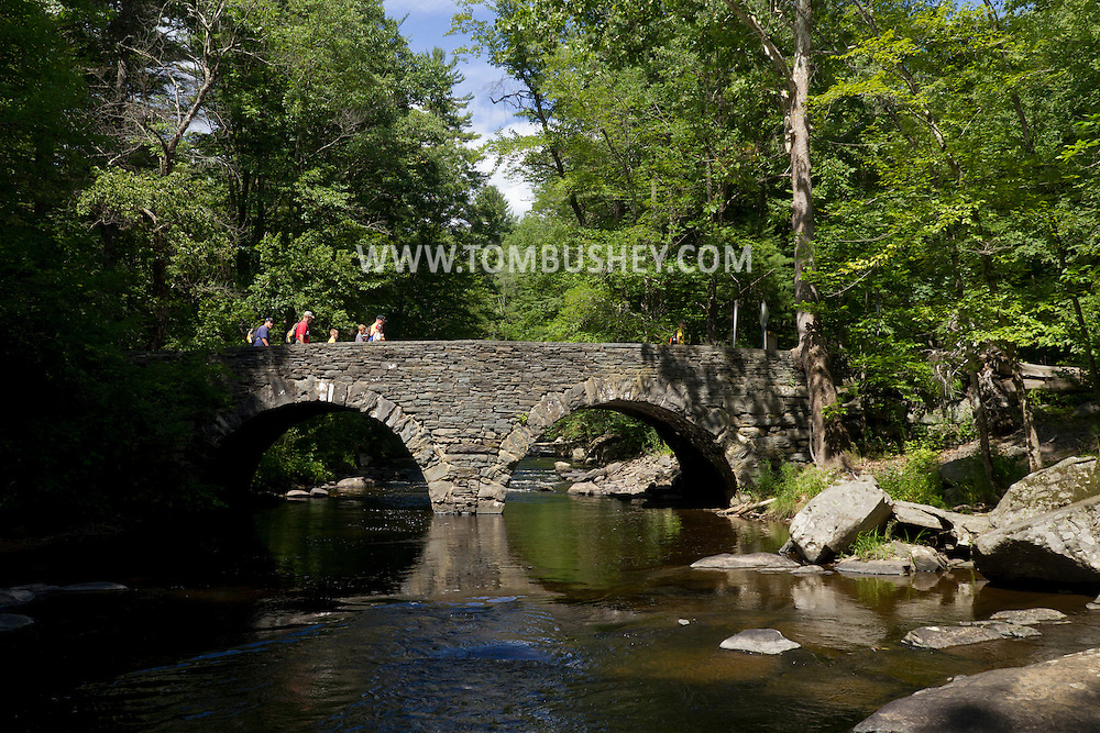 Tusten, New York - People walk across a stone arch bridge over the Ten Mile River on July 24, 2014. The bridge was constructed in<br /> 1875 when industry at Tusten included<br /> lumbering and the quarrying of bluestone.