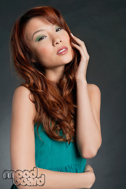 Portrait of beautiful Asian woman posing over colored background