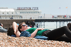 © Licensed to London News Pictures. 22/05/2016. Brighton, UK. Members of the relax on the Beach in Brighton as the weather in the South Coast is warming up again after several colder days. Photo credit: Hugo Michiels/LNP