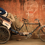 A bicycle rickshaw driver take a mid-day nap on his passenger's seat near New Dlehi train station