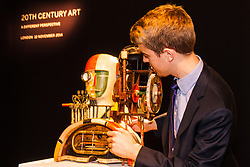 "London, November 7th 2014. Sotheby's is to hold its Inaugural 20TH Century Art– A Different Perspective sale on November 12th in London, where collectors will have the opportunity to acquire some highly regarded examples of avante-garde and abstract art. PICTURED: Sotheby's Richard Lowkes examines Georg Hartmann's ""Mechanical Head"", which is expected to fetch between £15,000 to £20,000 at auction."