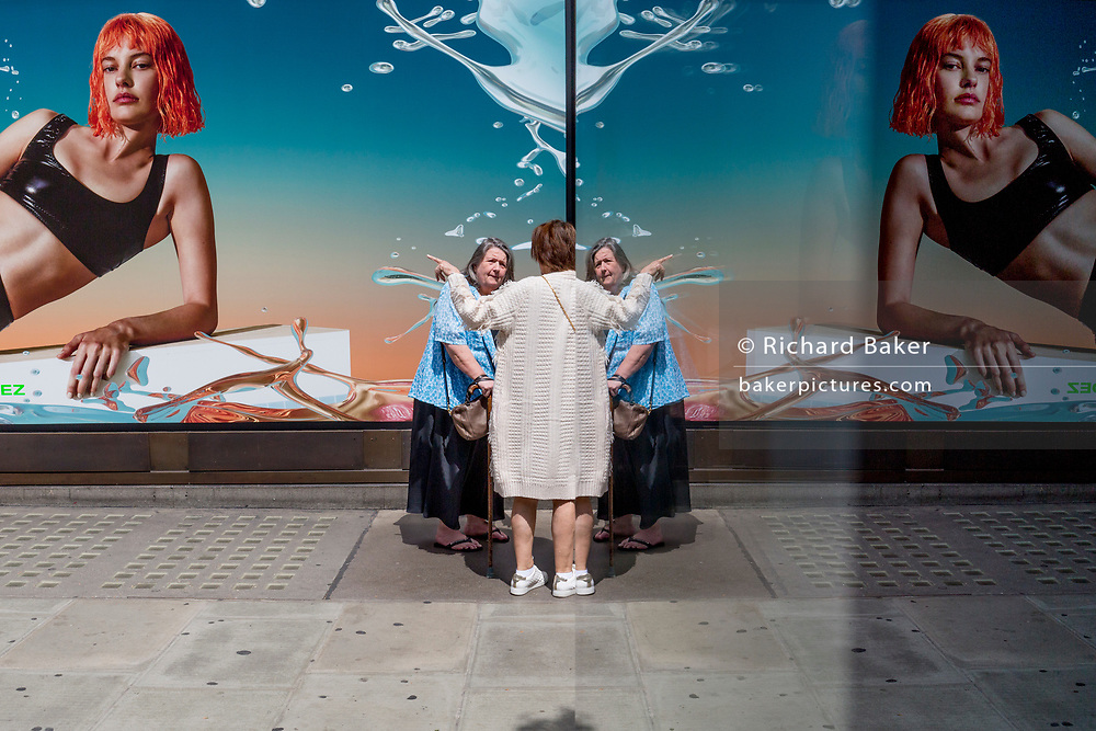 Middle-aged women talk either side of the symmetrical reflection of a young female model in an advert outside the London location of the Selfridges Department store on Oxford Street, on 2nd July 2019, in London, England.