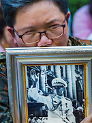 13 OCTOBER 2016 - BANGKOK, THAILAND:  A mourner holds a portrait of the King of Thailand just before the King's death was announced at Siriraj Hospital. Thousands of people came to the hospital to pray for the beloved monarch. Bhumibol Adulyadej, the King of Thailand, died at Siriraj Hospital in Bangkok Thursday, October 13, 2016. Bhumibol Adulyadej, 5 December 1927 – 13 October 2016, was the ninth monarch of Thailand from the Chakri Dynasty and is known as Rama IX. He became King on June 9, 1946 and served as King of Thailand for 70 years, 126 days. He was, at the time of his death, the world's longest-serving head of state and the longest-reigning monarch in Thai history.      PHOTO BY JACK KURTZ