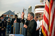 Freeport, New York, USA. September 10, 2014. A pastor gives a blessing at a dockside remembrance ceremony in honor of victims of the terrorist attacks of September 11 2001, at the boat Miss Freeport V, on Freeport's Nautical Mile. Further ceremonies were held on board the vessel, which sailed from the Woodcleft Canal on the South Shore of Long Island, on the eve of the 13th Anniversary of the 9/11 attacks.