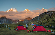 Sunrise illuminates the Cordillera Huayhuash above Carhuacocha campground (13,600 feet) in the Andes Mountains, Peru, South America. Peaks from left to right are: Yerupaja Grande (6635 m or 21,770 ft, highest point in the Amazon watershed), Yerupaja Chico, and Mount Jirishanca (Icy Beak of the Hummingbird). Day 3 of 9 days trekking around the Cordillera Huayhuash.