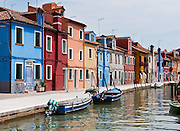 "Blue boats, canal, and houses painted blue, red, orange, yellow. Burano, known for knitted lacework, fishing, and colorfully painted houses, is a small archipelago of four islands linked by bridges in the Venetian Lagoon, northern Italy, Europe. Burano's traditional house colors are strictly regulated by government. The Romans may have been first to settle Burano. Romantic Venice (Venezia), ""City of Canals,"" stretches across 117 small islands in the marshy Venetian Lagoon along the Adriatic Sea in northeast Italy, between the mouths of the Po (south) and Piave (north) Rivers. Venice and the Venetian Lagoon are honored on UNESCO's World Heritage List."