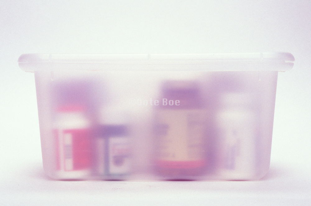plastic container box containing various medicine and vitamin bottles