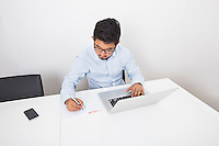 Young businessman writing while using laptop at desk in office