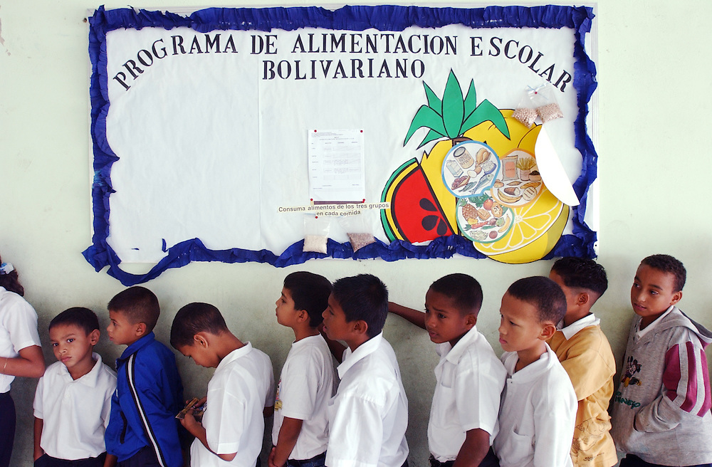 "Students at the Florencio Jimenez school wait in line for lunch.  The school is one of the new ""Bolivarian"" Schools which are part of President Chavez's Education Reform.  The new Bolivarian Schools keep students for an entire day, as opposed to a half day, feed the students lunch and offer programs like drama, art and music.  The sign above the students reads ""Bolivarian School Food Program"".  While President Chavez touts his programs that benefit the poor, many point to a rising poverty rate and shrinking economy and claim the programs fail to substantially help."