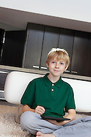Portrait of pre-teen boy using tablet pc at home