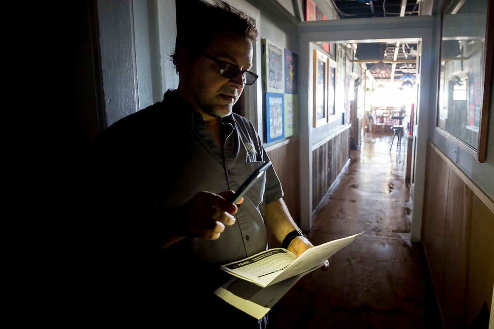 John Yarbrough, the owner of Spanky's restaurant on Tybee Island, Ga., uses the light from his cell phone to read paperwork, Tuesday, Sept., 12, 2017, after storm surge from Tropical Storm Irma knocked out power and flooded his restaurant yesterday. (AP Photo/Stephen B. Morton)