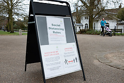 © Licensed to London News Pictures. 29/03/2020. London, UK. A sign displays information about social distancing for dog walkers and joggers in Greenwich Park  . The Government has announced a lockdown to slow the spread of Coronavirus and reduce pressure on the NHS. Photo credit: George Cracknell Wright/LNP