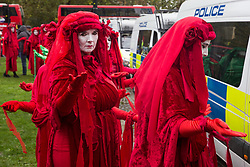 London, UK. 12 October, 2019. The Red Brigade assemble with thousands of fellow climate activists from Extinction Rebellion to take part in the XR funeral march from Marble Arch to Russell Square on the sixth day of International Rebellion protests to demand a government declaration of a climate and ecological emergency, a commitment to halting biodiversity loss and net zero carbon emissions by 2025 and for the government to create and be led by the decisions of a Citizens' Assembly on climate and ecological justice. Credit: Mark Kerrison/Alamy Live News