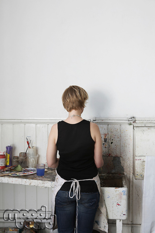 Rear view of young woman cleaning paintbrushes at sink