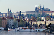 A tourist excursion boat passing Charles Bridge and the Hradschin (Castle Mountain) on the Vltava river.
