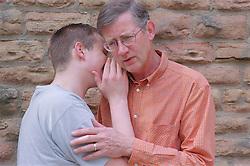 Teenage boy whispering in man's ear,
