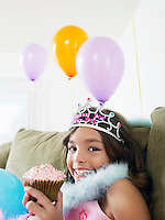 Young girl (7-9) sitting on sofa eating cupcake close-up