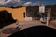 Children play basketball in Juanacatlán, Guerrero on April 16th, 2010. At the background there are visible sterile zones in the hills.  (Photo: Prometeo Lucero)