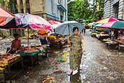 12 JUNE 2013 - YANGON, MYANMAR:  A Burmese woman walks through a rainy season thunderstorm in Yangon, Myanmar.        PHOTO BY JACK KURTZ