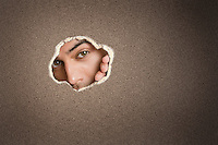 Portrait of a young Asian male peeking from paper hole