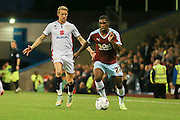 Burnley defender Tendayi Darikwa holds the ball away from Milton Keynes Dons midfielder Carl Baker during the Sky Bet Championship match between Burnley and Milton Keynes Dons at Turf Moor, Burnley, England on 15 September 2015. Photo by Simon Davies.