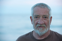 Portrait of an older man by the ocean at dusk