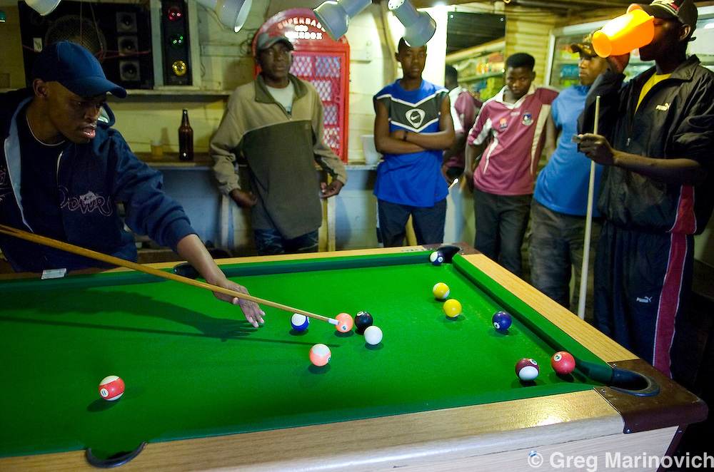 South African and West African youth play pool in an illegal bar n Imizamo Yethu shanty town, Hout Bay, Cape Town, South Africa. The work of the CPF and neighbourhood watch have seen the crime rate in Hout Bay drop 63%, but relations between the shanty town of Imizamo Yethu and Hout Bay are tense.  photo  Leonie Marinovich