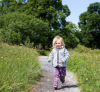 Girl (3-4) running on path in countryside