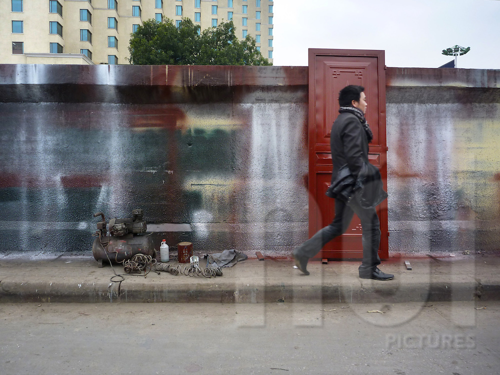 Hanoi, Vietnam.Right next to the luxury hotel Sofitel Plaza, on the other side of the dike road, walls are used as backgrounds for objects painting.