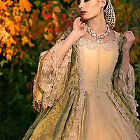 A brunette young woman dressed in a fancy vintage dress standing in front of colorful autumn trees