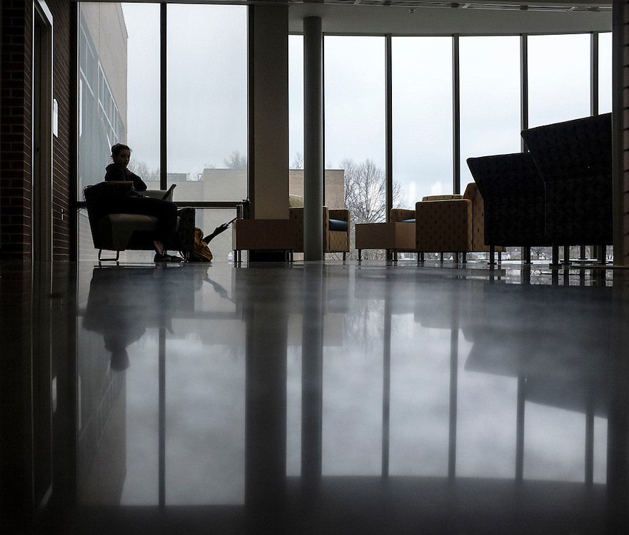 A student studies between classes in the lounge on the second floor of the new Flight and Technology Building.