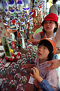 Children look at glass wind chimes, known locally as Edo Furin, on sale at an outdoor market in Shimoda, Japan. The traditional chimes, which were until not long ago carried around town by sellers on bamboo poles, date back more than 200 years in Japan. Today there are but a handful of makers left in Japan, with cheaper imports from Korea and China gaining the lion's share of the business for these popular summer decorations. The chimes sold here are made at Tokyo-based Shinohara Furinhonpo, a family business has been in operation for over 100 years andmakes around 200,000 of the chimes a year.