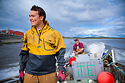 Austen Erickson stands in the front of the family boat as his dad, Jeff, drives them out to sea to check on fish nets in Unalakleet, Alaska.