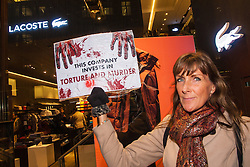 "London, November 28th 2014. Animal rights campaigners demonstrate outside the Regent Street branch of up-market fashion brand Lacoste who they accuse of using Chinese-bred angora rabbit fur in some of their garments. They allege that angora rabbits have their fur pulled out while pinned down, alive. Several months later the same rabbits are subjected once again to the same cruelty and are eventually killed for their pelts. PICTURED: An animal rights campaigner accuse Lacoste of investing in the ""torture and murder"" of angora rabbits."