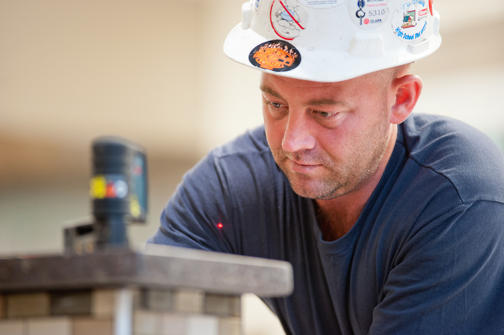 A construction worker uses a laser straight edge to help level out large countertop pieces.