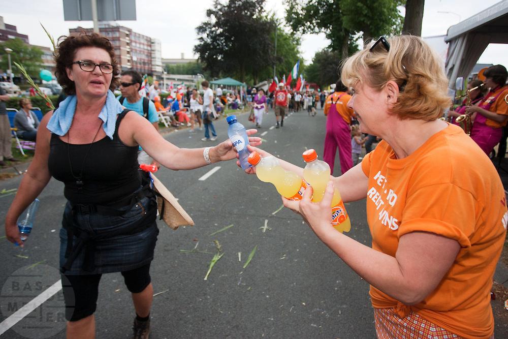Een medewerker van de bloedbank biedt een wandelaar van de Nijmeegse Vierdaagse drinken aan