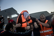 A gruop of migrants desimbarking carring an elderly woman on their shoulders after crossing the Aegean Sea. FEDERICO SCOPPA/CAPTA
