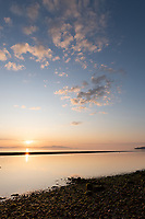 The sunrise over the sandbar at Cordova Bay rises in golds and reds on a calm ocean, with the sandbar gloriously peaceful.