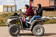 CANADA, Nunavut<br /> Young Inuit woman on quad with family