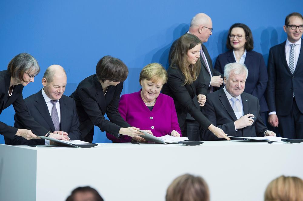 12 MAR 2018, BERLIN/GERMANY:<br /> Horst Seehofer (L), CSU, desig. Bundesinnenminister, Angela Merkel (M), CDU, Bundeskanzlerin, und Olaf Scholz (R), SPD, desig. Bundesfinanzminister, und drei Damen des Protokolls, Unterzeichnung des Koalitionsvertrages der CDU/CSU und SPD, Paul-Loebe-Haus, Deutscher Bundestag<br /> IMAGE: 20180312-02-015