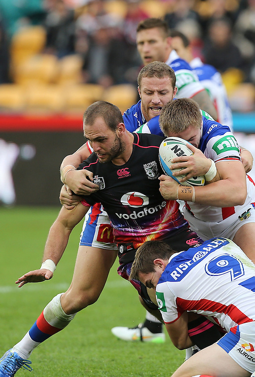 Captain Simon Mannering of the New Zealand Warriors is tackled by Korbin Sims of the Newcastle Knights and Jack Stockwell and Adam Clydsdale during their round 12 NRL match at Mount Smart Stadium, Auckland on  Sunday, May 31, 2015. Credit: SNPA / David Rowland